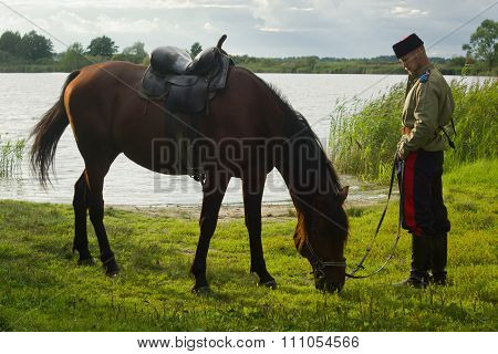 Russian Cossack With A Horse Resting On The Lake