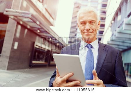 Senior businessman holding touchpad outdoors