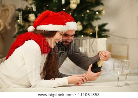 Happy Couple On The Background Of The Christmas Tree At Home Celebrating By Opening A Bottle Of Cham