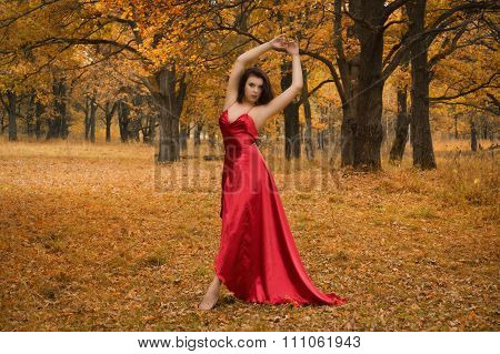 Girl In A Red Dress Dancing In The Autumn Forest