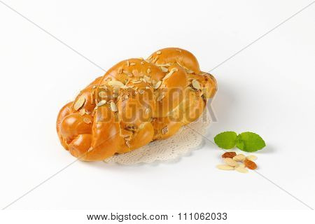 loaf of sweet braided bread with almonds and raisins on lace place mat