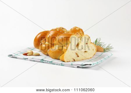half of sweet braided bread on checkered dishtowel