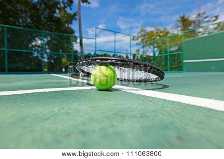 Tennis ball and racquet on the court close-up