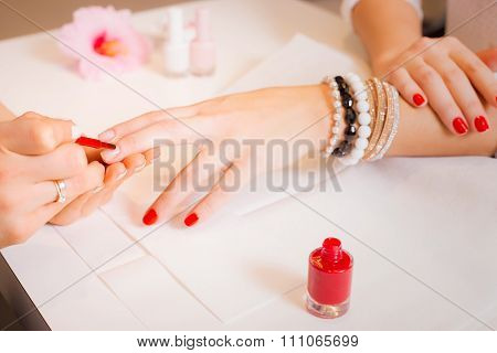 Woman painting clients nails red