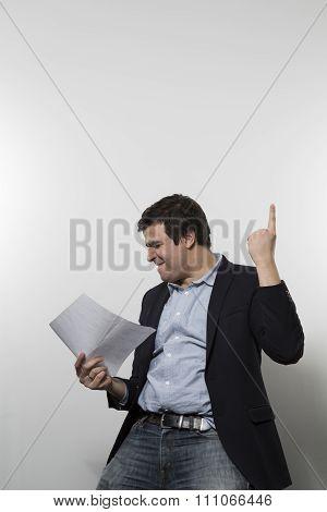 studio shot of happy businessman celebrating a paper