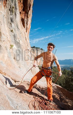 Rock Climber Holding Belay Rope Over The Mountains