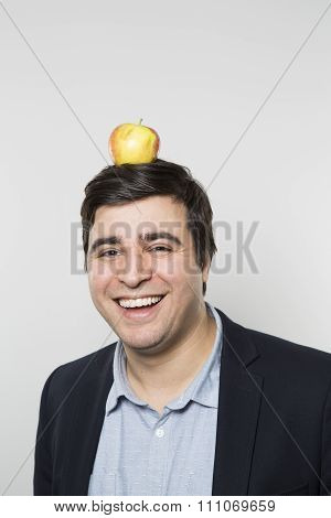 studio shot of happy person with an apple on his head