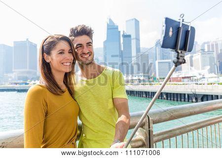 Caucasian couple take self photo by selfie stick