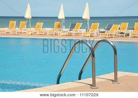 Hotel Swimming Pool With Stair, Yellow Longes And Umbrellas