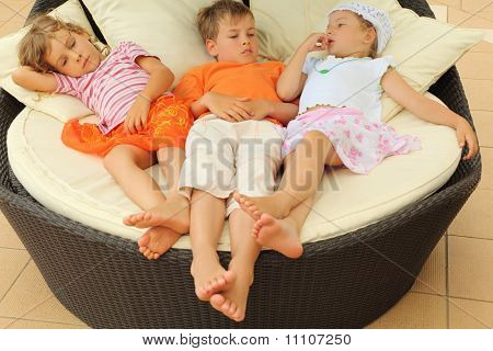 Two Tired Little Girls And Boy Lying On Big Circle Armchair With Pillows And Having Rest
