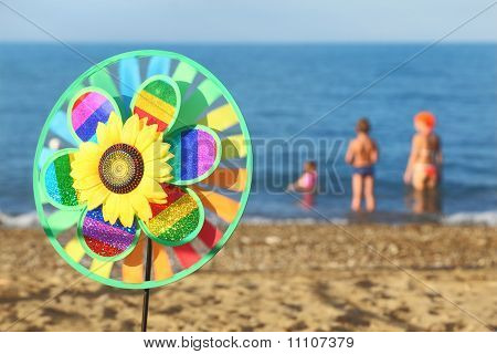 Multicolored Pinwheel Toy With Flower On Beach, Family Standing In Water