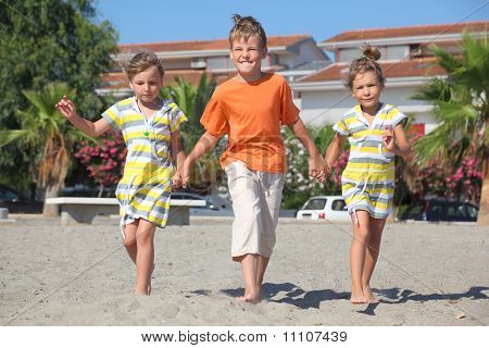 Little Boy And Two Girls Walking On Beach, Holding For Hands, Palms And Building