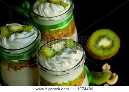Natural Sweet Dessert With Kiwi And Nuts In Glass Jars On Kitchen