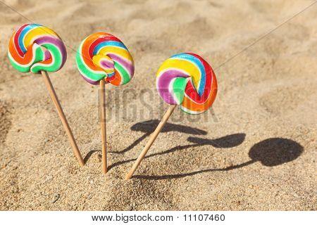 Three Multicolored Lollipops Sticked In Sand On Beach, Sunny