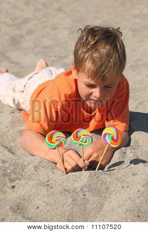 Caucasian Boy In Orange Shirt Lying On Beach, Multicolored Lollipops Stick Into Sand