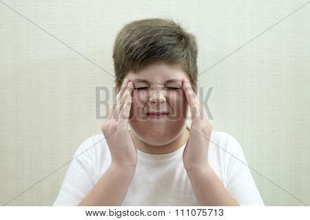 Portrait of  teenage boy with a headache