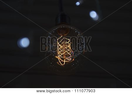 Closeup Of A Vintage Electric Incandescent Lamp In Black Background