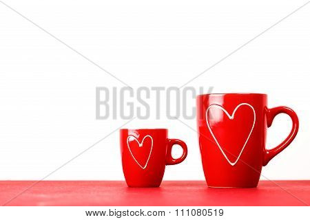 Two red cups of tea or coffee with hearts