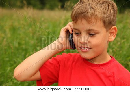 Little Boy In Red Shirt Talking On Cell Phone Outdoors. Boy Smiles