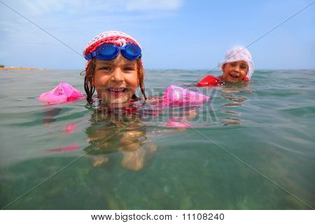 Two Little Sisters Are Swimming In Sea. One Girl In Blue Glasses For Swimming