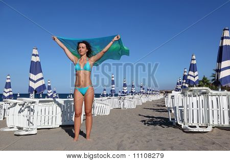 Beautiful Young Woman In Blue Swimsuit And Pair Stands On Beach. In Background Rows Of Deck Chairs