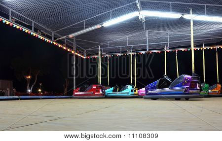 Amusement Car Ride. Several Colorful, Bright Cars. Dark Night.