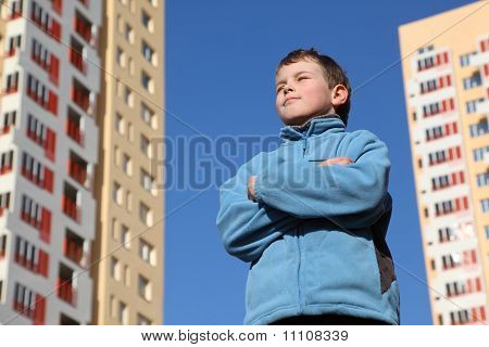 Little Boy With Closed Eyes In Blue Jacket. In Background Two Multi-story Yellow Houses And Blue Sky