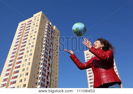 Beautiful Young Woman In Red Jacket Playing With Balloon In Form Of Globe, Multi-storey Yellow House