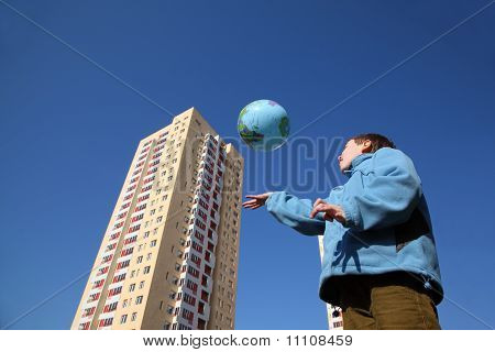 Little Boy In Blue Jacket Playing With Balloon In Form Of Globe, Multi-storey Yellow House