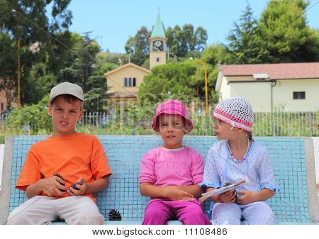 Little Brother And Two Sisters Are Sitting On A Blue Bench. Boy Holding A Cone