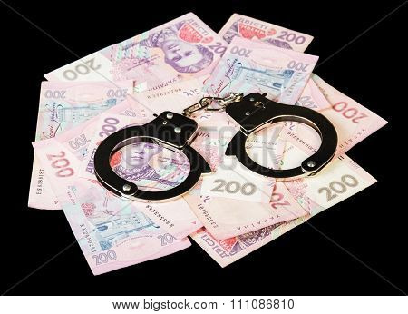 Ukrainian hryvnia with handcuffs close up isolated on a black ba