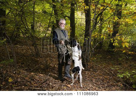 Men Looking For Truffles In The Woods With His Dog