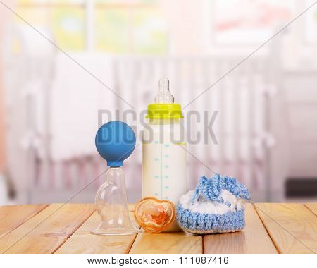 Jar with milk, booties and nipple close-up on a table in the chi
