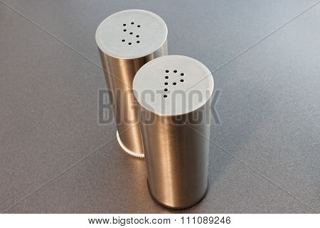 Stainless steel salt and pepper shakers on grey background