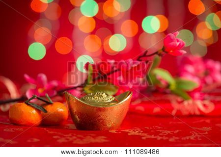 Chinese new year festival decorations, gold ingot, plum flower and mandarin orange on red glitter background.