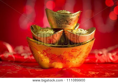 Chinese new year festival decorations, gold ingots on red glitter background.