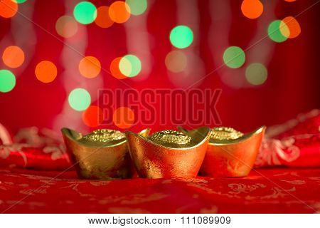 Chinese new year festival decorations, gold ingots on red glitter background with copy space on top.