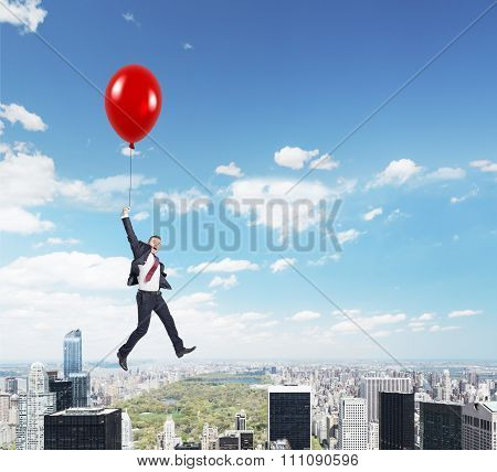 Man Flying With Balloon Over City
