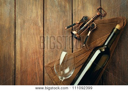Bottle of wine with glass and corkscrew on wooden background
