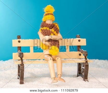 The wooden man figure on bench in the freezing snow
