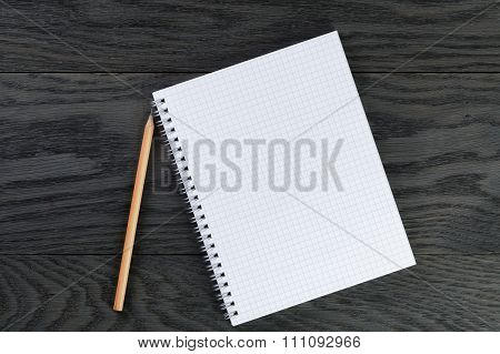 blank notepad with chequered pages on gray wood table with pencil