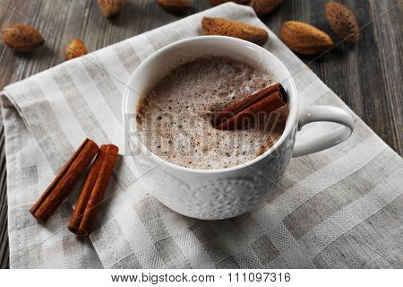 Cup of hot cacao on cotton serviette with cinnamon and almonds