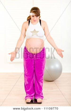 Dissatisfied with her weight pregnant woman standing on weight scale at home
