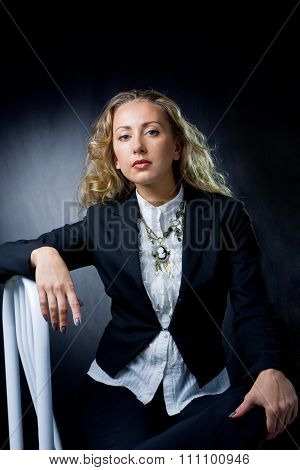 a young woman sitting on chair.  studio shot