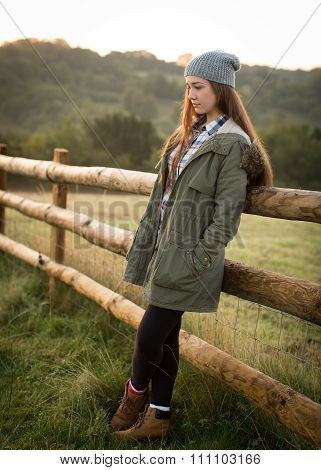 Beautiful Teen Girl Leaning Against A Farm Fence