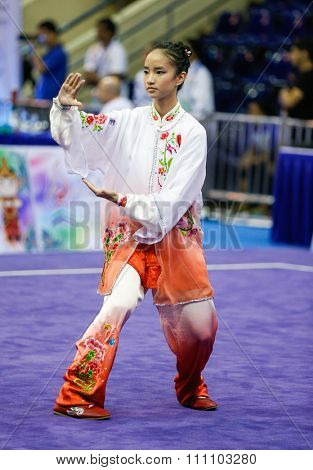 JAKARTA, INDONESIA - NOVEMBER 16, 2015: Vera Tan of Singapore performs her movements in the Women's Compulsory Taijiquan event at the 13th World Wushu Championship 2015 held in Istora Senayan Stadium.