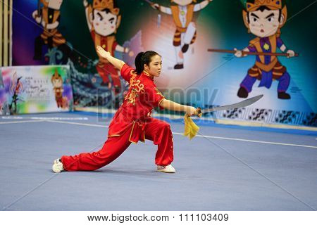 JAKARTA, INDONESIA - NOVEMBER 16, 2015: Ami Li of the USA performs the movements in the women's Daoshu event at the 13th World Wushu Championship 2015 at the Istora Senayan Stadium.