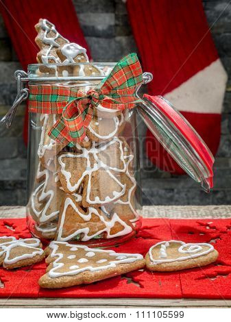 Assorted Christmas gingerbread cookies with white icing in glass jar on table
