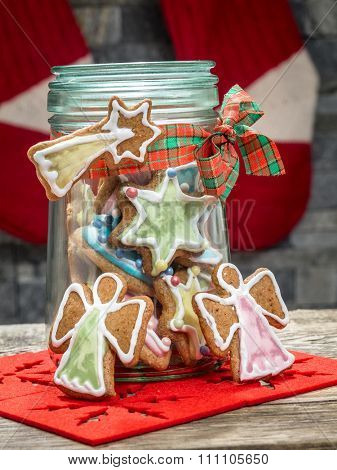 Assorted Christmas gingerbread cookies with colorful icing in glass jar on table