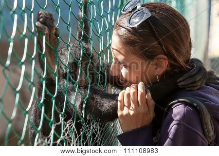 Portrait Of A Young Woman Playing And Hugging Spider Monkey